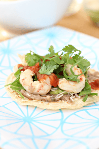 Delicious Mexican style shrimp tostados. Loaded with beans, guacamole and other delicious toppings.
