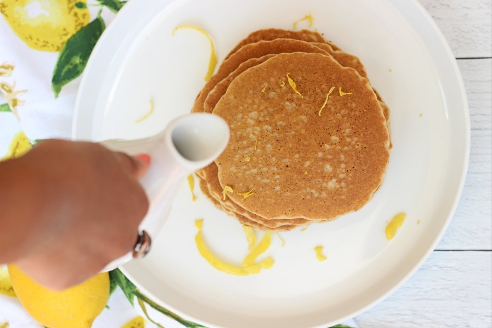 pouring syrup on gluten free dairy free lemon pancakes