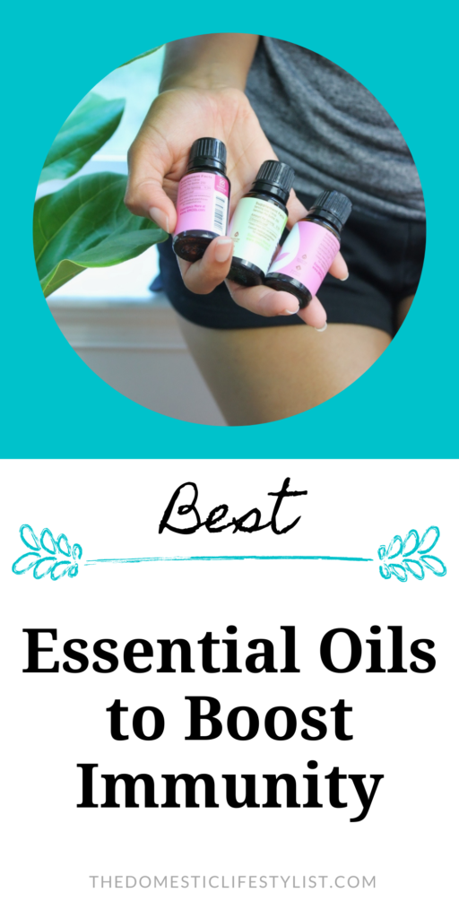 Hand holding three bottles of essential oils to boost immunity