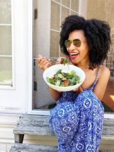 Healthy mom sitting and eating a salad