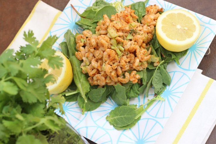 plate of shrimp salad with old bay and a lemon