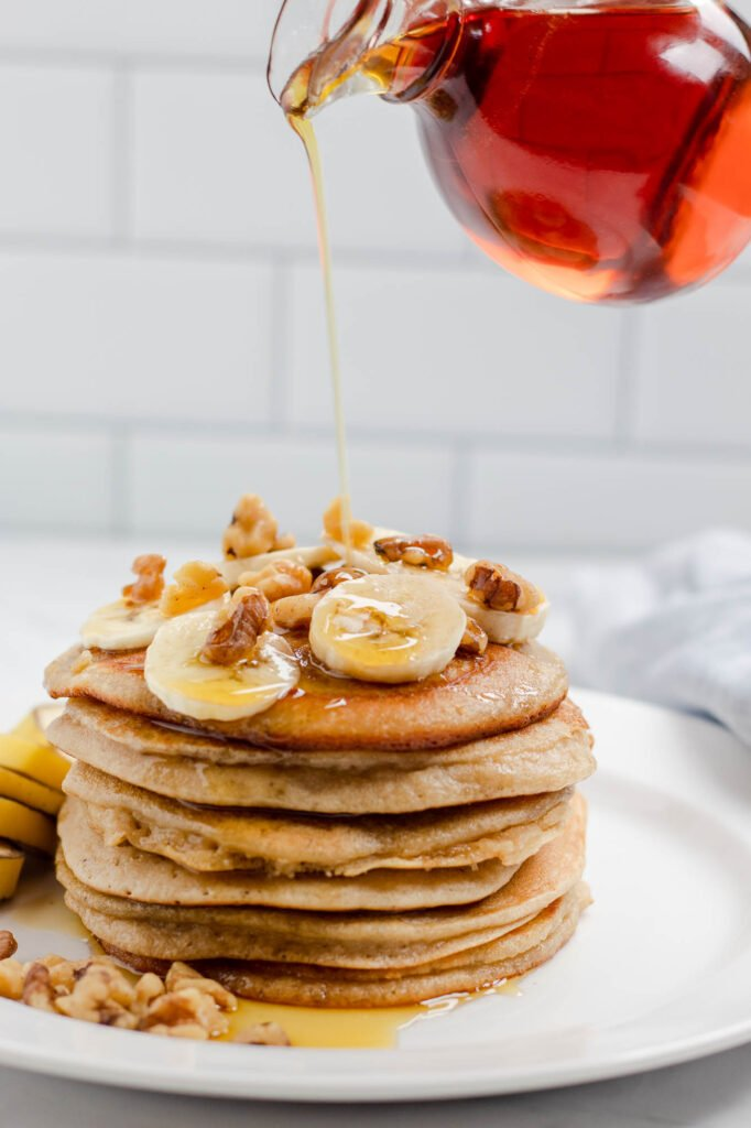 stack of almond flour banana pancakes dripping with maple syrup
