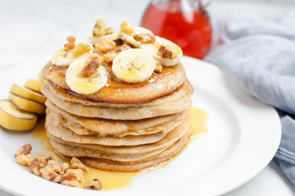 stack of almond flour banana pancakes topped with bananas and walnuts